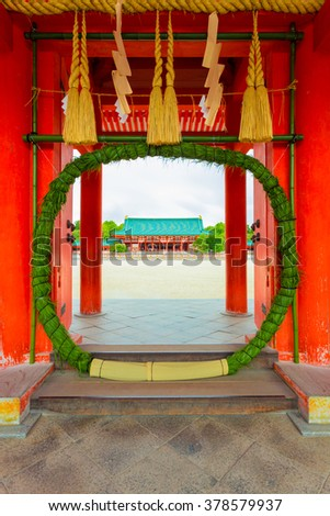 Green chinowa-kuguri, a round reed ring wreath for purification at entrance gate into Heian-Jingu Shrine showing inner courtyard and Taikyokuden main building in Kyoto, Japan. Vertical - stock photo