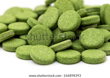 Green chlorophyll tablets on white background  - stock photo