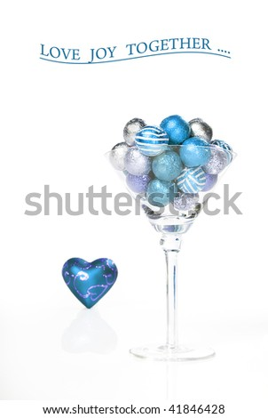 Green chocolate balls in a martini glass with a heart on white background with space for text - stock photo