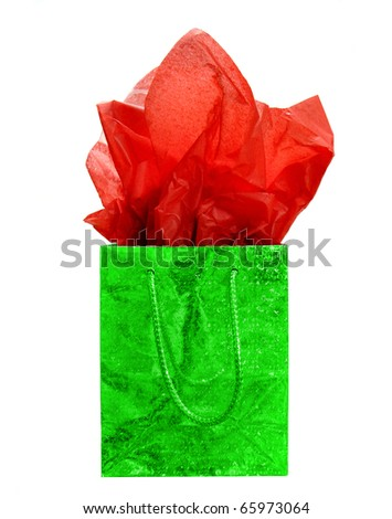 Green Christmas gift bag with red tissue paper - stock photo