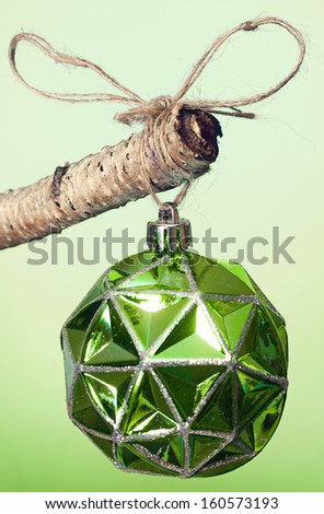 Green Christmas ornament hanging  on a tree branch. - stock photo
