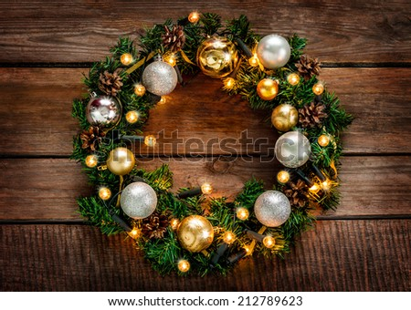 Green christmas wreath decorated with gold balls, lights and pinecones on an old vintage planked wood background - rustic style - stock photo