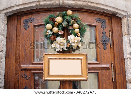 Green christmas wreath decorated with gold balls on wooden door and frame with place for your text - stock photo