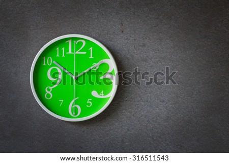 Green clock over gray grunge background - stock photo