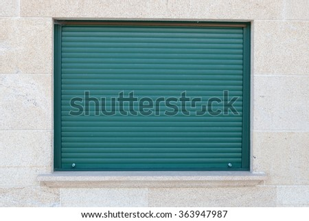 Green closed metal shutter on a window of a stone house - stock photo