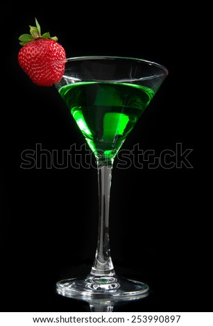 Green cocktail absinth decorated with red strawberry in martini cocktails glass for halloween night party isolated on a black background - stock photo