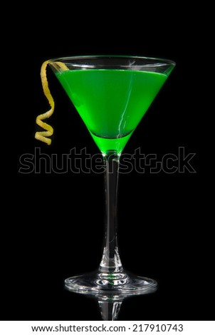 Green cocktail with absinth decorated with lemon twist in martini cocktails glass for halloween night party isolated on a black background - stock photo
