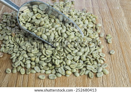 Green coffee beans in metal scoop on vintage wooden surface - stock photo