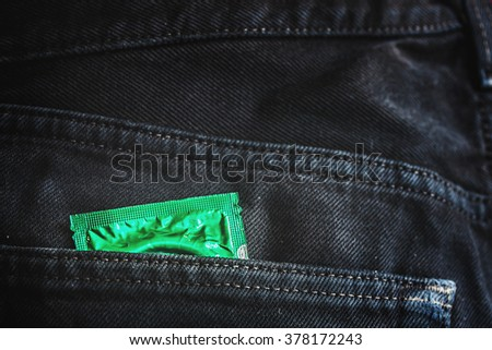 green condom pack in back pocket jeans,abortion concept. - stock photo