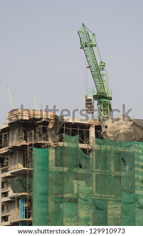 Green construction cranes are building. - stock photo