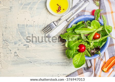 Green country  salad in blue bowl on rustic kitchen table background, top view, place for text. Healthy  lifestyle or detox diet food  concept - stock photo