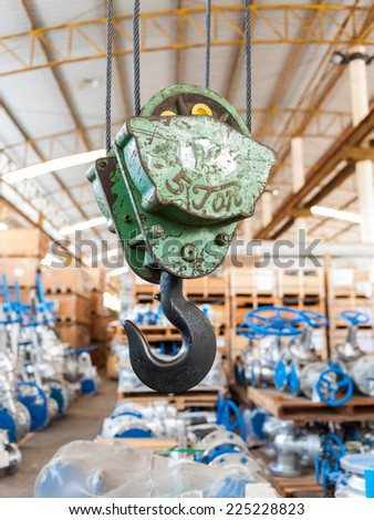 Green crane hook with some industrial valve on the background - stock photo