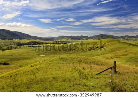 green cultivated pasture in a secluded valley at Barrington tops surrounded by distant mountain heads on a summer sunny day - stock photo
