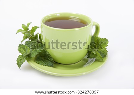 Green cup of  tea with lemon balm herb on a white background. - stock photo