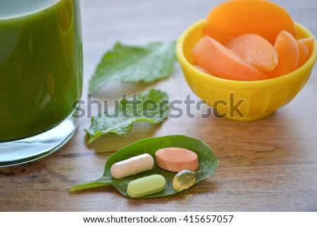 Green detox smoothie, dietary supplements and a serving of apricots on wooden table - stock photo