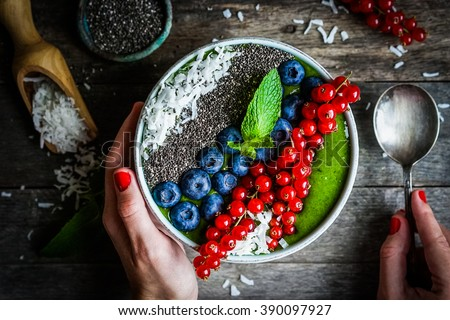 Green detox smoothie with berries on wooden background bowl - stock photo