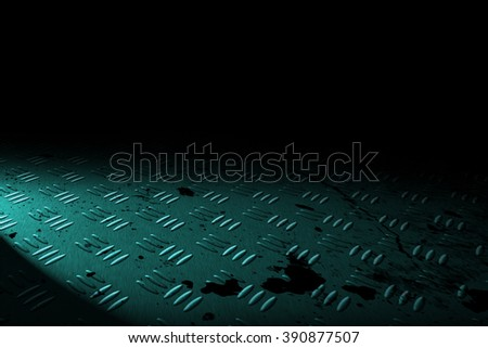 green diamond plate with spot lighting and drop of paint on black shadow background. - stock photo
