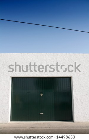 green door garage, white wall and blue sky, sidewalk and street - stock photo
