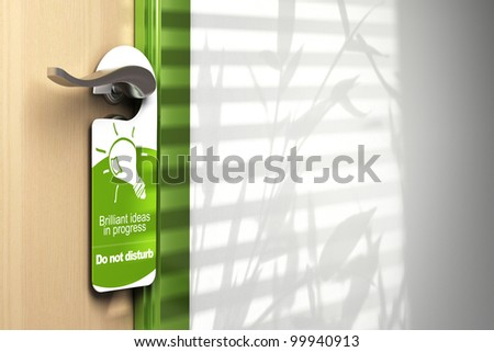 green door hanger onto a handler with room for text on the wall at the right side. On the sign it's written brilliant ideas in progress, do not disturb - stock photo