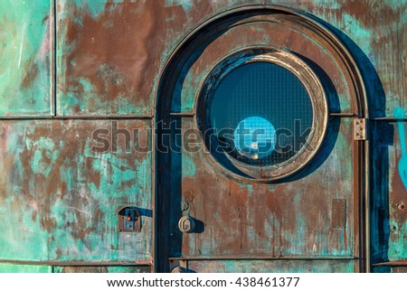 Green door with glass round circular window. Grunge texture of green rusty metal with spots, stains. Turquoise control tower of the Knippelsbro bascule bridge. Colored metallic textured background. - stock photo