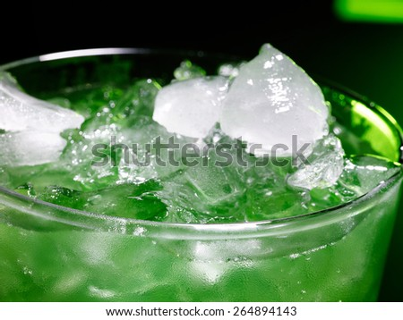 Green drink  with crushed ice on dark background. Top view.Close up. - stock photo
