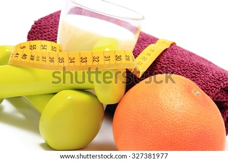 Green dumbbells and purple towel for using in fitness, fresh grapefruit, glass of milk and tape measure, concept for slimming, healthy nutrition and lifestyle - stock photo