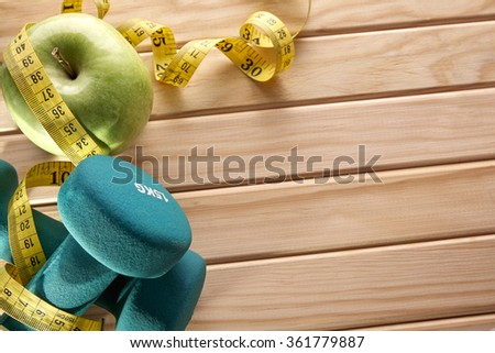 Green dumbbells, apple and tape measure on wooden floor. Concept health, diet and sports. Horizontal composition. Top view - stock photo