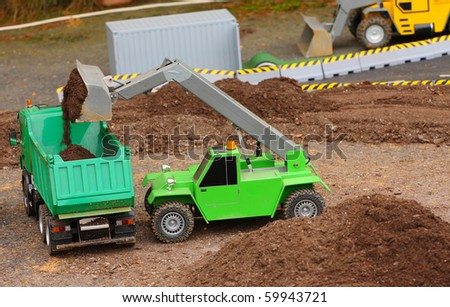 Green dumper and earthmover on a road building. Homemade RC model - plastic kit (  scratchbuild 1 : 32 scale) - stock photo