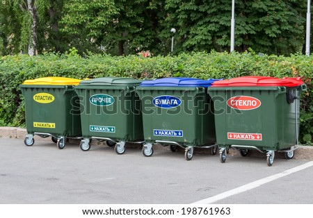 """Green dumpsters on a city street with inscription on russian: """" Plastic"""", """"Other"""", """"Paper"""", """"Glass"""", """"Press on"""" - stock photo"""