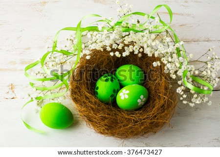 Green Easter eggs in a nest with green satin ribbon and small white baby's breath flowers on a white wooden background, top view. Easter eggs. Easter. Easter background - stock photo