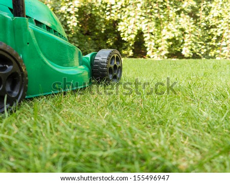 Green Electric Lawnmower on Grass - stock photo
