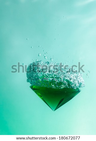 Green emerald falling through the water against a green background - stock photo
