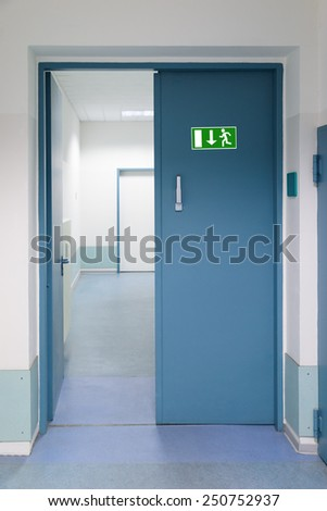 Green Emergency Evacuation Sign On Metal Door - stock photo
