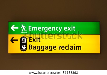 green emergency exit and yellow exit/baggage claim sign at a international airport - stock photo
