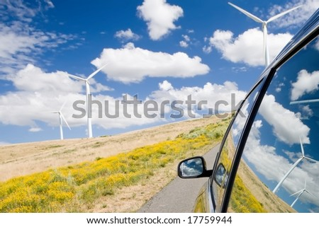 Green energy concept with wind turbines reflected in a car window - stock photo
