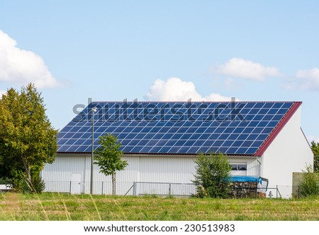 Green energy with solar collectors on the roof of an agricultural building - stock photo