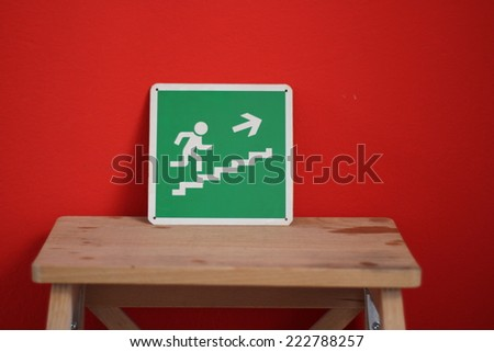 green exit sign along red wall - stock photo