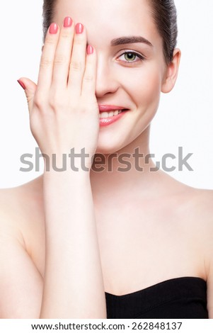 Green-eyed young beautiful woman in black dress closing eye by hand and smiling - stock photo