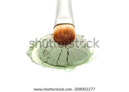 Green eyeshadow powder with brush on white background - stock photo