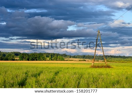 Green field against dark stormy clouds - stock photo