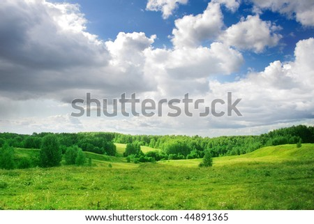 Green field and blue sky with white clouds. - stock photo