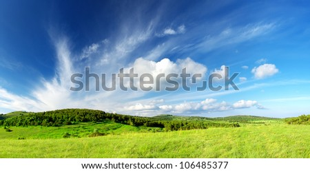 Green field and large sky with clouds. Bright summer landscape - stock photo