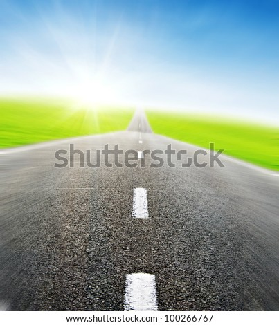 green field and road over blue sky in motion- travel and tranportation concept - stock photo
