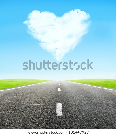 green field and road over blue sky with clouds in shape of  heart - honeymoon travel concept - stock photo
