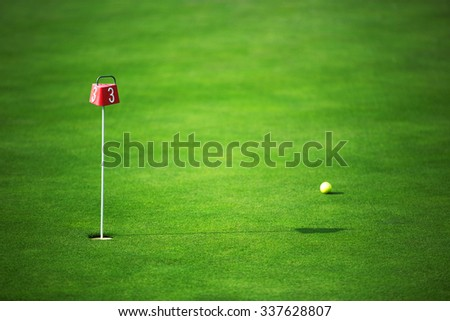 Green field, golf course and ball near the hole - stock photo