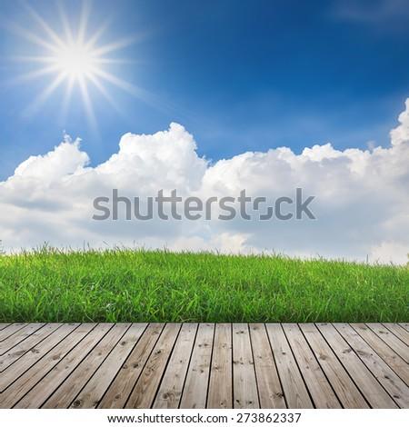 Green field under blue sky with sun beam. Wood floor - stock photo