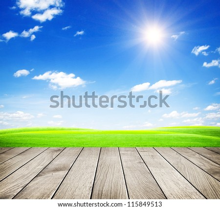 Green field under blue sky. Wood floor - stock photo