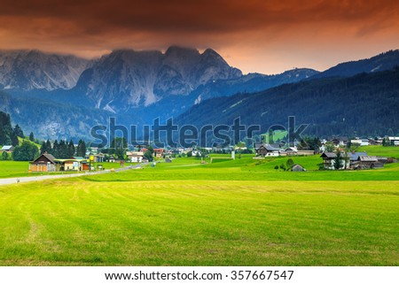 Green fields and famous touristic town with high Dachstein mountain group,Gosau,Austria,Europe - stock photo