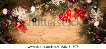 green fir branches on the wooden floor with darkening at the edges with Christmas decorations - stock photo