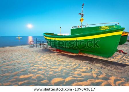 Green fishing boat on the beach of Baltic sea, Poland - stock photo